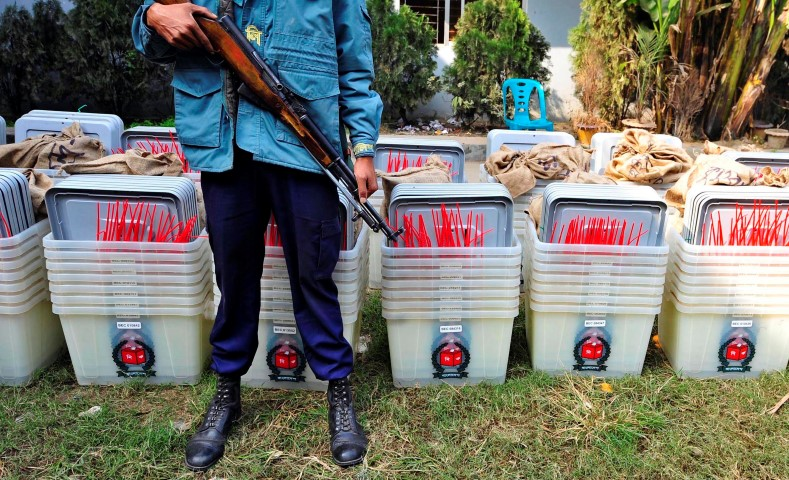 A member of the police stands guard in front of ballot boxes at a distribution centre ahead of parliamentary elections in Dhaka