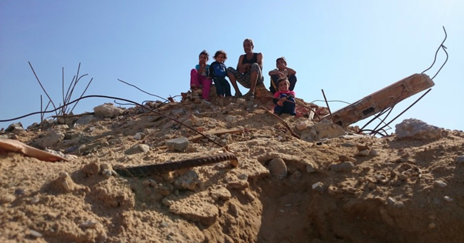 2014: Kamal and his children on the rubble of their twice-destroyed home. (Photo: Jen Marlowe)