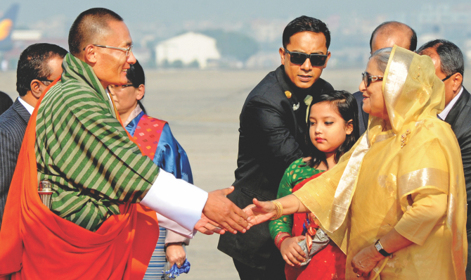 Prime Minister Sheikh Hasina welcomes her Bhutanese counterpart Tshering Tobgay at Hazrat Shahjalal International Airport yesterday. Photo: BSS