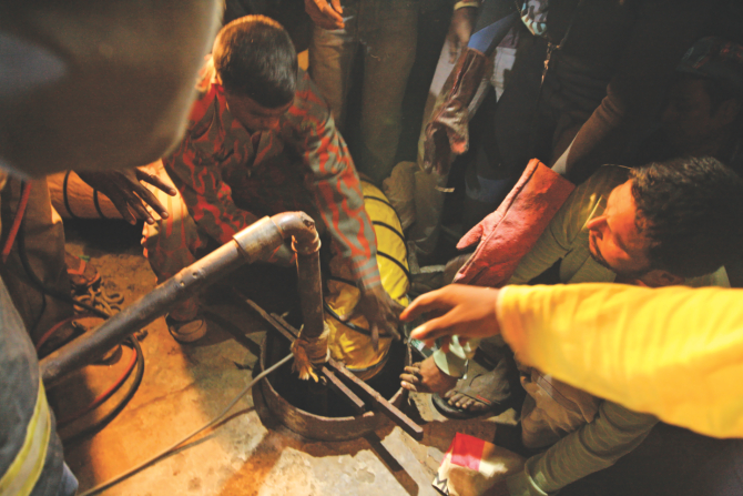Rescuers pump in oxygen into the well shaft using a pipe and try to get a child, who had fallen in the shaft, out by tying a sack at the end of a rope and lowering it in at Shahjahanpur Railway Colony in the capital yesterday. Photo: Palash Khan