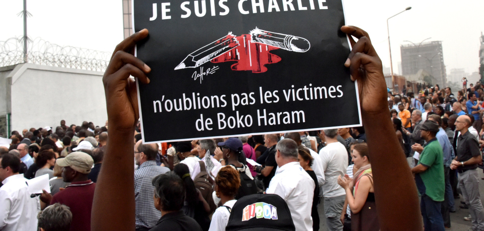 "A man holds a placard that reads ""Je suis Charlie, n'oublions pas les victimes de Boko Haram"" (I am Charlie, let's not forget the victims of Boko Haram) as people gather outside the French embassy in Abidjan, on January 11, 2015, in tribute to the 17 victims of the three-day killing spree in Paris last week. The killings began on January 7 in Paris with an assault on the Charlie Hebdo satirical magazine in Paris that saw two brothers killing 12 people including some of the country's best-known cartoonists and the storming of a Jewish supermarket on the eastern fringes of the capital which killed 4 local residents. AFP PHOTO / SIA KAMBOU         (Photo credit should read SIA KAMBOU/AFP/Getty Images)"