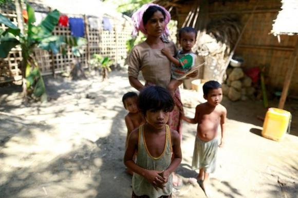 A Rohingya Muslim family, whose members have all fallen sick, poses in a village at Maungdaw