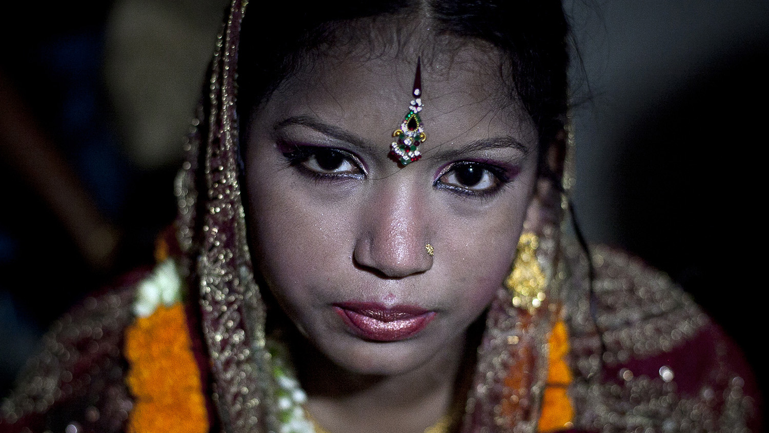 "13 year old Runa Akhter is seen the day of her wedding to a 29 year old man August 29, 2014 in Manikganj, Bangladesh. Runa was in the 7th grade, and loved reading, sports and traveling. She wanted to wait until she was 21 to get married but, ""No boy want's to marry a girl older than 18 in my village"" she said. In June of this year, Human Rights Watch released a damning report about child marriage in Bangladesh. The country has one of the highest rates of child marriage in the world, with 29% of girls marrying before the age of 15, and 65% of girls marrying before they turn 18. The detrimental effects of early marriage on a girl cannot be overstated. Most young brides drop out of school. Pregnant girls from 15-20 are twice as likely to die in childbirth than those 20 or older, while girls under 15 are at five times the risk. Research cites spousal age difference as a significant risk factor for violence and sexual abuse. Child marriage is attributed to both cultural tradition and poverty. Parents believe that it ""protects"" girls from sexual assault and harassment. Larger  dowries are not required for young girls, and economically, women's earnings are insignificant as compared to men's."